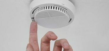 hand touching smoke alarm